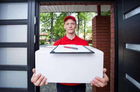 Delivery man giving a parcel to a client photo