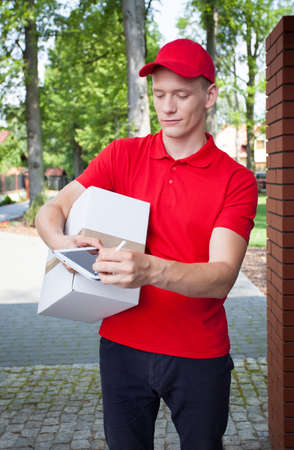 Delivery man carrying a box and looking at tablet photo