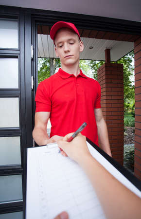 Delivery guy holding papers while woman signs photo
