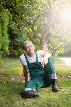 dungarees: Gardener in dungarees sitting on the grass Stock Photo