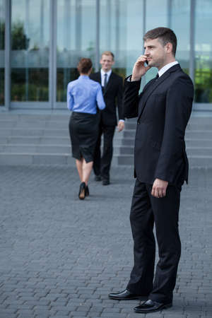 phonecall: A businessman standing in front of the building and having a phonecall