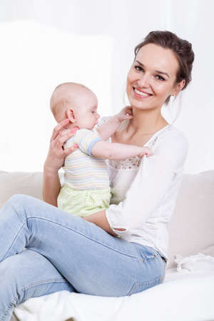 progeny: Young mother holding newborn baby in arms Stock Photo