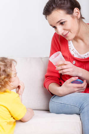 sick kid: Image of mum giving syrup to son