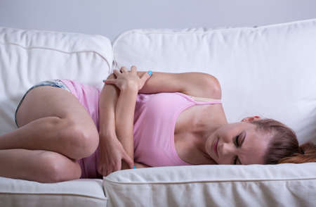 Young girl curled up on the couch having abdominal cramps photo