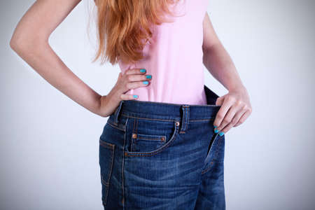 Dieting woman trying on her old big jeans photo