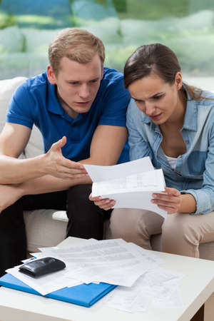 pay check: Marriage with high bills to pay, vertical Stock Photo