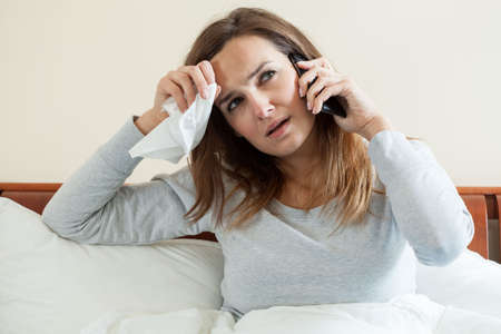 sick person: Ill woman talking on the phone, horizontal