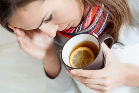 drinking tea: Ill woman in bed drinking lemon tea