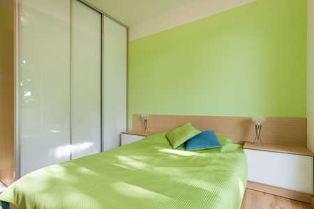 Spatial green bedroom with big bed in central part photo