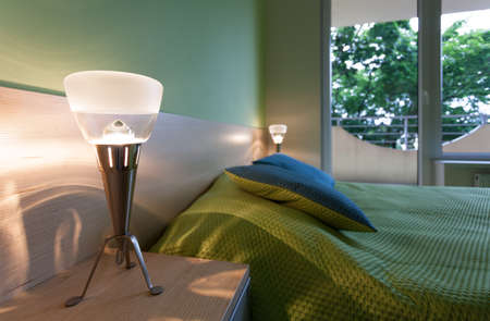 bedside lamps: Bright green bedroom with modern bedside lamps