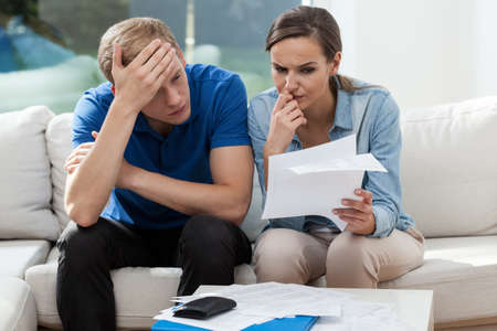budget crisis: Horizontal view of couple analyzing family bills Stock Photo