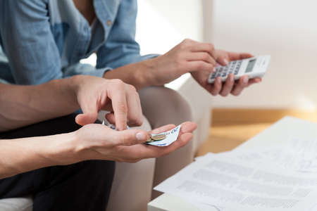 View of couple calculating money at home photo