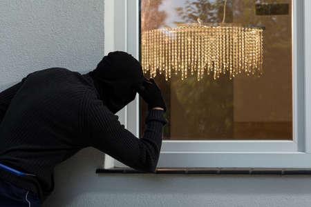 Burglar looks into house through the window Stock Photo