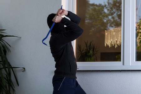 obscured: Burglar with obscured face trying to break the window Stock Photo