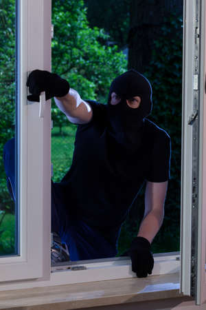 Masked man entering the house trough the window photo