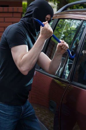 Masked robber breaks car window with a crowbar