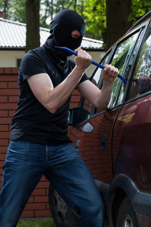 car crime: Criminal smashing a glass and breaking into a car