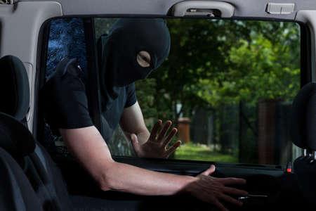 robo de autos: Ladrón con la cara oscurecida cerradura del coche abierta