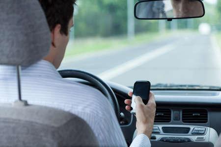 Man met behulp van telefoon tijdens het rijden van een auto