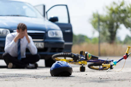 niños en bicicleta: Conductor sentado en la calle después de accidente de tráfico