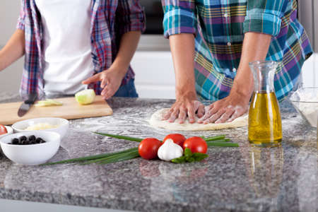 View of couple preparing pizza at home photo