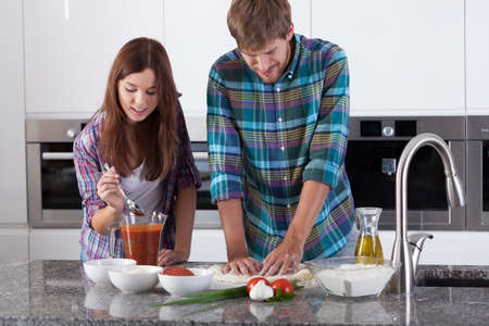View of couple making pizza at home photo