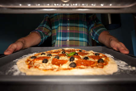 put: View of man putting pizza into oven