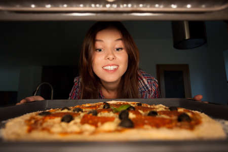 Happy girl putting pizza into oven, horizontal