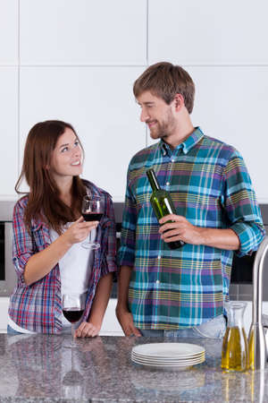 Couple drinking wine in the kitchen, vertical photo