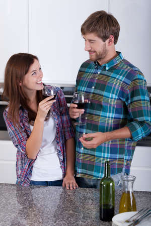 Loving couple drinking wine in the kitchen photo
