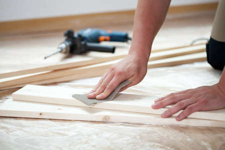 Male hands polishing wooden plank with sandpaper