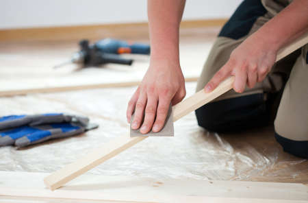Male hands using sandpaper for polishing wooden plank photo