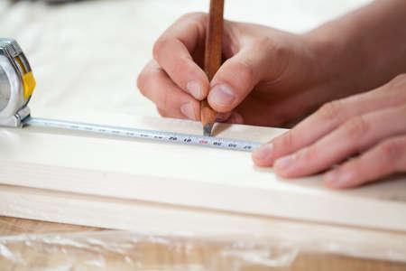 metro de medir: Primer plano de un hombre de manos con cinta de medición en la tabla de madera