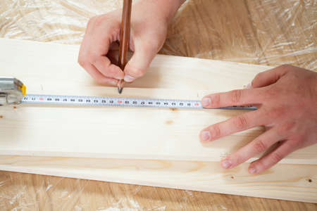 Male hands measuring wooden plank with measuring tape and pencil photo