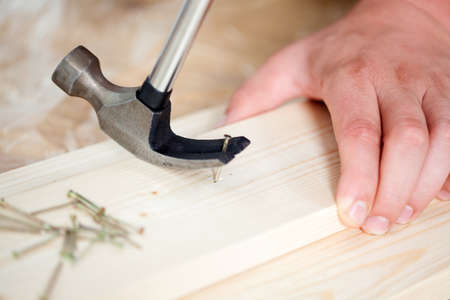 Close-up of removing nail from wooden plank using hammer photo