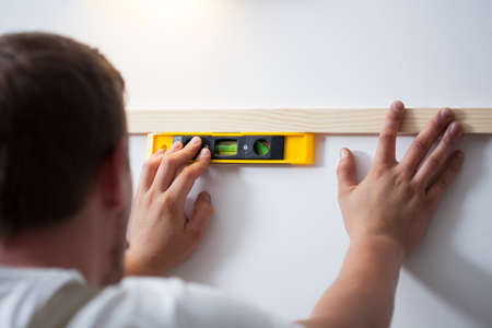 Back view of a man using spirit level at home photo