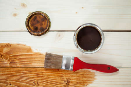 Paint can and paintbrush on wooden planks, horizontal photo