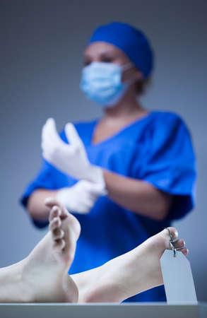 lifeless: Nurse and dead body in morgue, vertical Stock Photo