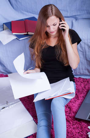 Teen girl talking with friend by phone before exam photo