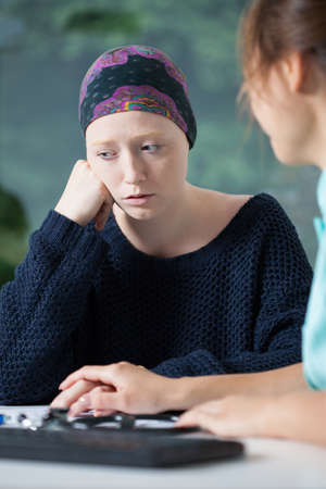Woeful woman suffering from cancer talking with doctor