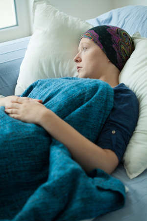 headscarf: Young woman with headscarf lying in hospital bed Stock Photo
