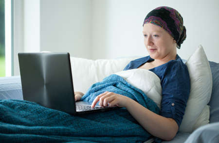 Smiling cancer girl using laptop in bed