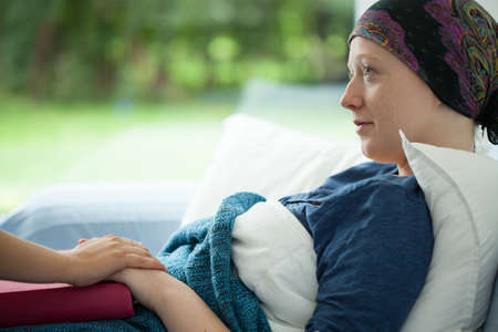 Cancer woman lying in bed supported by mum Imagens
