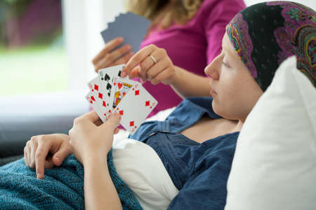 Cancer girl playing cards in hospital bed Stock Photo - 32304651