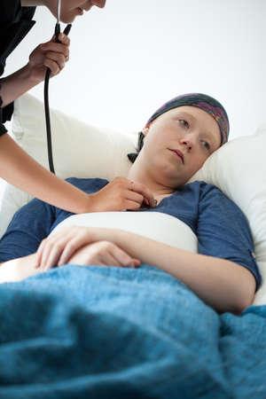 leucemia: Doctor que examina a la mujer joven que sufre de neoplasia