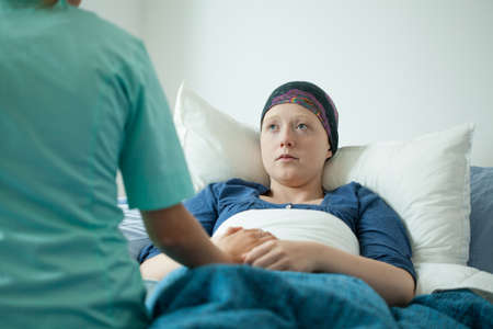 Ill with cancer girl talking with doctor photo