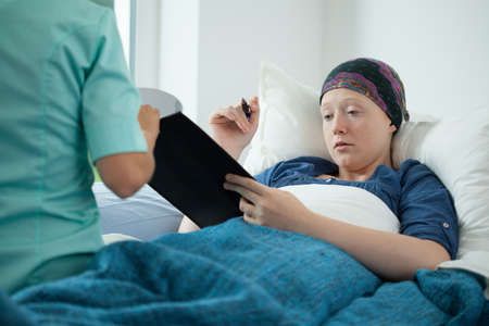 bald girl: Cancer young woman signing documents in hospital