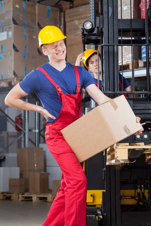 accident at work: Man with a backache in a factory