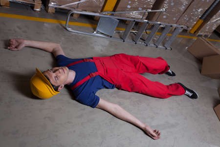 Unconscious man on the floor in a factory photo