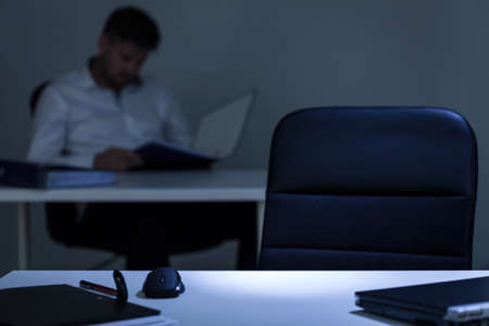 lonliness: Man sitting in the background of empty office desk